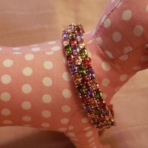 Multi colored gems set in rose gold bangle